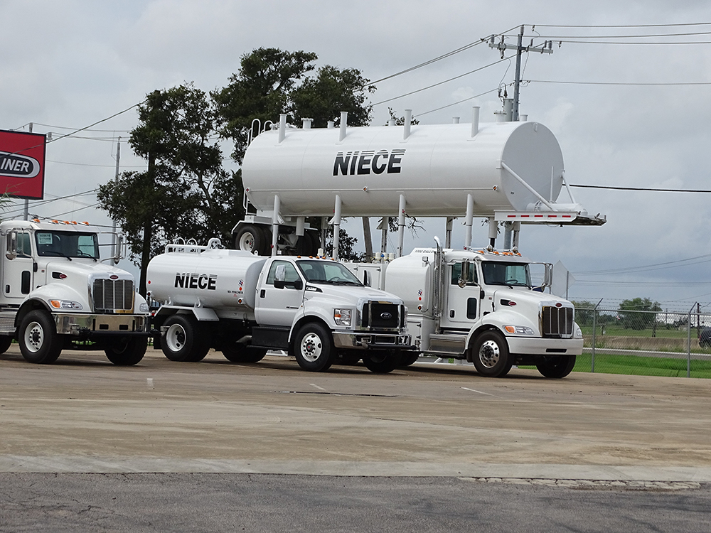 Image of Niece trucks lined up next to a Niece water tank